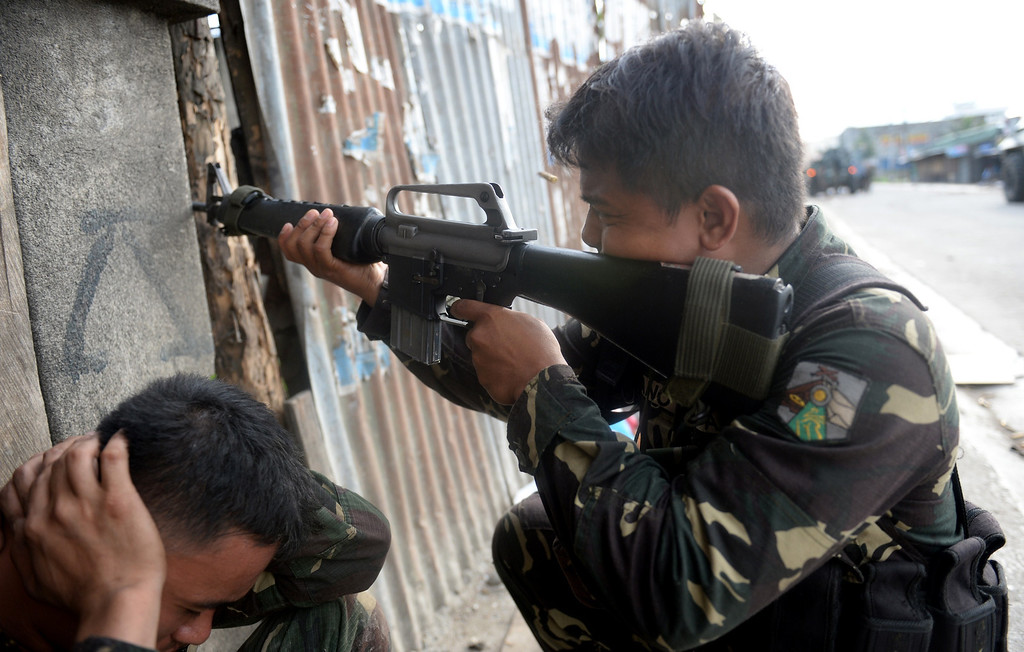 Description of . A Philippine soldier fires his M-16 rifle at rebels' snipers as another soldier covers his ears during a fire fight between government forces and Muslim rebels as stand-off entered its fourth day in Zamboanga City on the southern island of Mindanao on September 12, 2013.   AFP PHOTO/TED ALJIBE/AFP/Getty Images