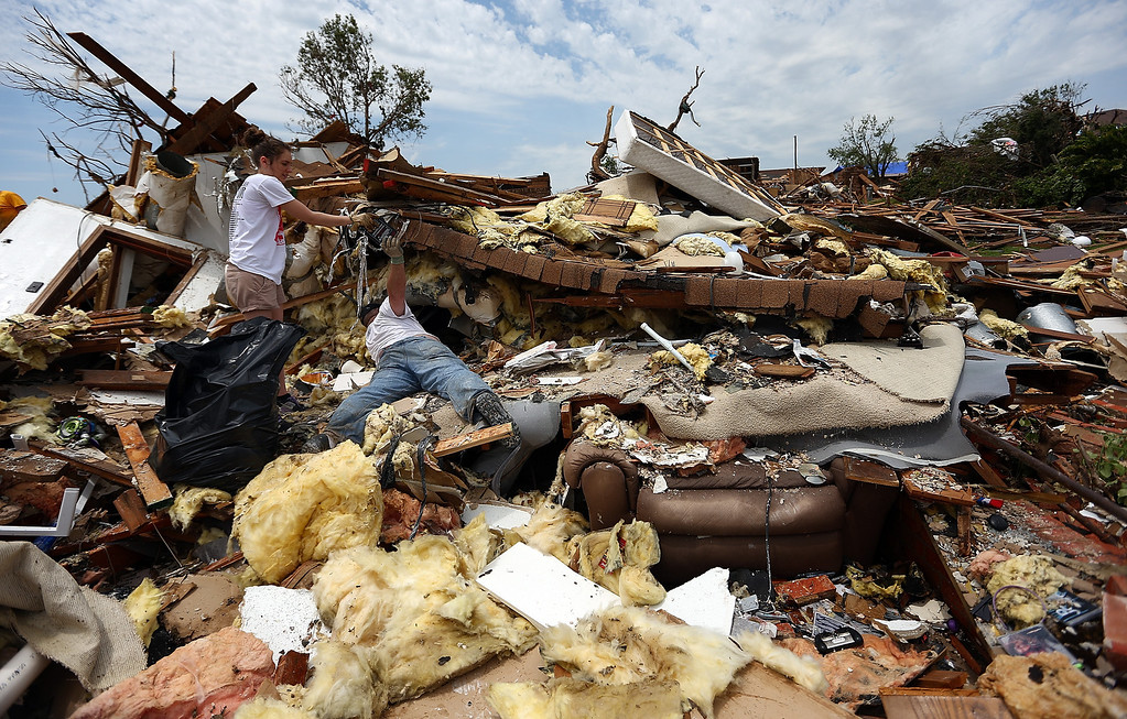 Description of . MOORE, OK - MAY 23:  (L-R) Taylor Trumble helps her neighbor, Moe Vaughan, search through the rubble of his house on May 23, 2013 in Moore, Oklahoma. The two-mile-wide Category 5 tornado touched down May 20 killing at least 24 people and leaving behind extensive damage to homes and businesses. U.S. President Barack Obama promised federal aid to supplement state and local recovery efforts.  (Photo by Tom Pennington/Getty Images)