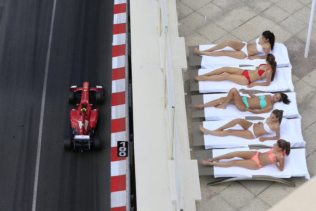 Description of . Women sunbathe as Ferrari's Brazilian driver Felipe Massa drives past during the third practice session at the Circuit de Monaco in Monte Carlo on May 25, 2013 ahead of the Monaco Formula One Grand Prix.  ALEXANDER KLEIN/AFP/Getty Images