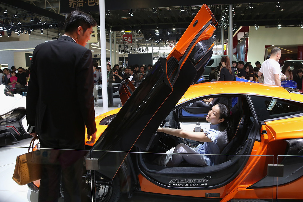 Description of . A potential consumer sits in a McLaren sport car during the 2014 Beijing International Automotive Exhibition at China International Exhibition Center on April 21, 2014 in Beijing, China. (Photo by Feng Li/Getty Images)