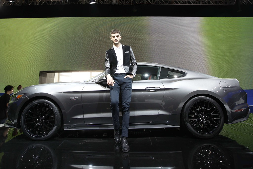 Description of . A model poses by a Mustang 50th anniversary edition car on display at the China International Exhibition Center new venue during the
