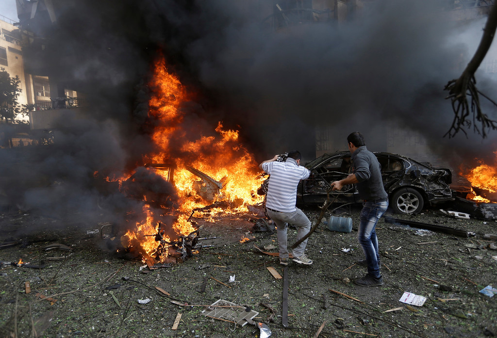 . Lebanese men stand in front of burned cars, at the scene where two explosions have struck near the Iranian Embassy killing many, in Beirut, Lebanon, Tuesday Nov. 19, 2013.  (AP Photo/Hussein Malla)