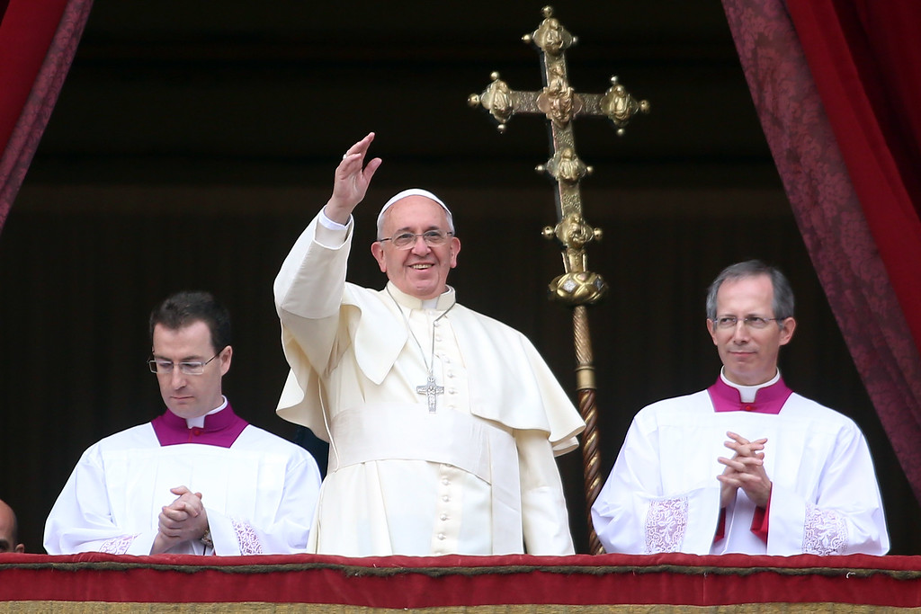 Description of . VATICAN CITY, VATICAN - DECEMBER 25:  Pope Francis waves to the faithful as he delivers his Christmas Day message from the central balcony of St Peter's Basilica on December 25, 2013 in Vatican City, Vatican. The 'Urbi et Orbi' blessing (to the city and to the world) is recognised as a Christmas tradition by Catholics with the Pope Francis focusing this year on the peace in the world.  (Photo by Franco Origlia/Getty Images)