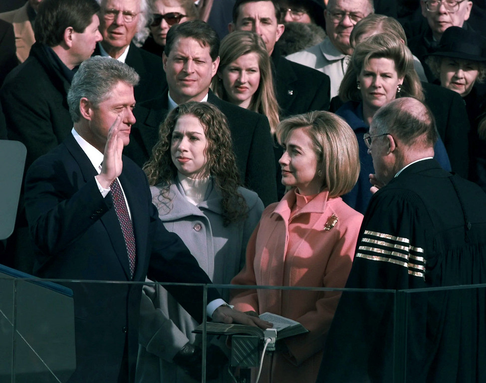 Description of . President Clinton is sworn in for his second term Monday, Jan. 20, 1997, in Washington by Chief Justice of the United States William Rehnquist as his wife Hillary and daughter Chelsea look on. (AP Photo/Doug Mills)