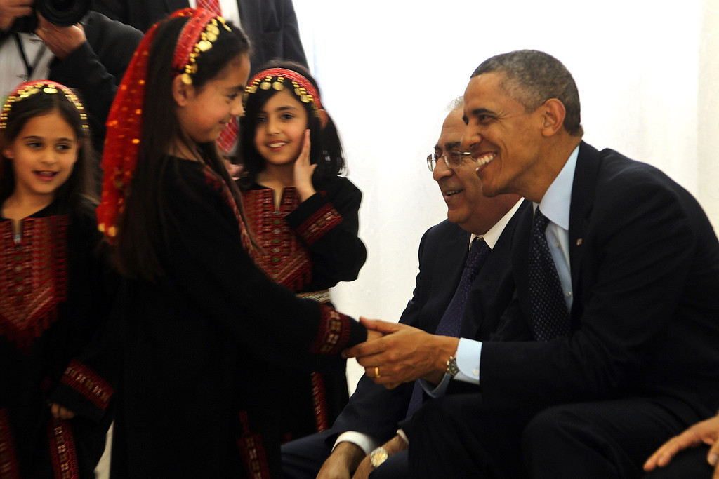 Description of . U.S. President Barack Obama (R) is welcomed by Palestinian girls during his visit to Al Bera Youth Center March 21, 2013 in Ramallah, the West Bank.   (Photo by Alaa Badarneh-Pool/Getty Images)