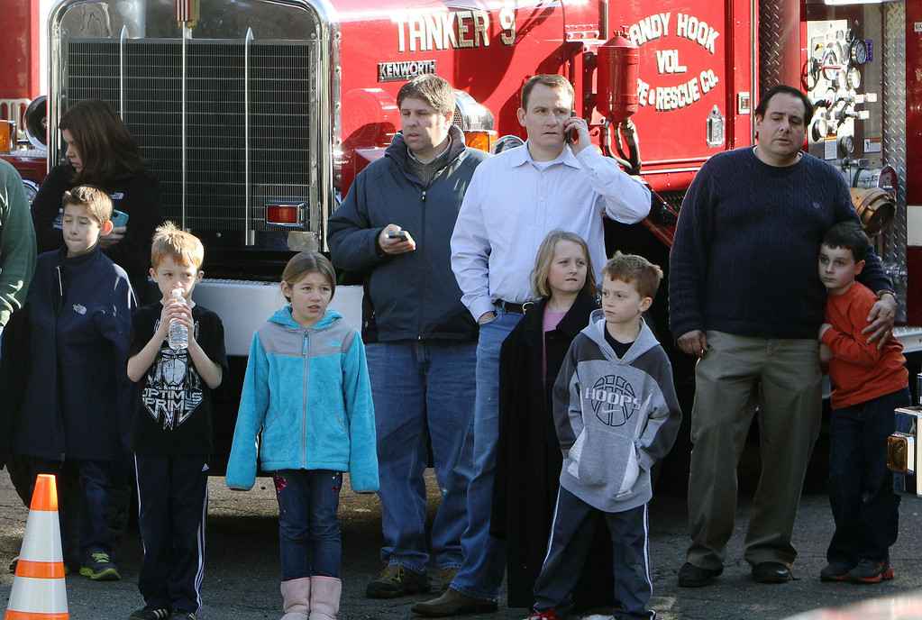 Description of . School children wait for their parents at the Sandy Hook firehouse following a mass shooting at the Sandy Hook Elementary School in Newtown, Conn. on Friday, Dec. 14, 2012. (AP Photo/The Journal News, Frank Becerra Jr.)