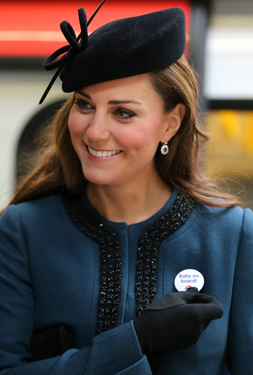 """Description of . Britain\'s Catherine, Duchess of Cambridge, wears a Transport For London (TFL) badge that reads \""""baby on board\"""", given to her during a visit to Baker Street tube station with Queen Elizabeth II and Prince Philip, Duke of Edinburgh, in London on March 20, 2013 to mark 150th anniversary of the London underground. The 86-year-old queen attended her first public engagement for more than a week after she had to cancel a number of events last week as she was still recovering from a bout of gastroenteritis which saw her admitted to hospital on March 3 for the first time in ten years.  Chris Radburn/AFP/Getty Images"""