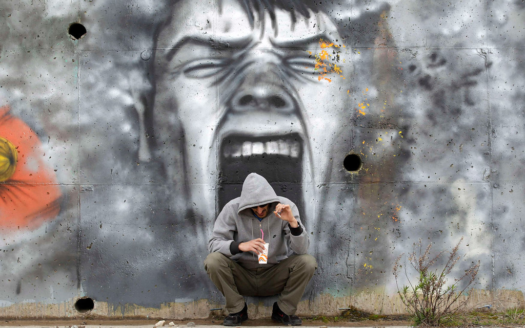Description of . A man drinks coffee in front of a mural near the coastal town of Kalamatta in the Messinia area of Greece March 23, 2012. REUTERS/Cathal McNaughton