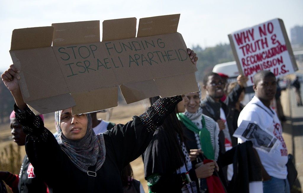 Description of . A woman holds a sign during a protest against the US president's visit to South Africa outside the university in Soweto on June 29, 2013. Police fired stun grenades today at hundreds of protesters rallying against President Barack Obama's visit to South Africa. ODD ANDERSEN/AFP/Getty Images