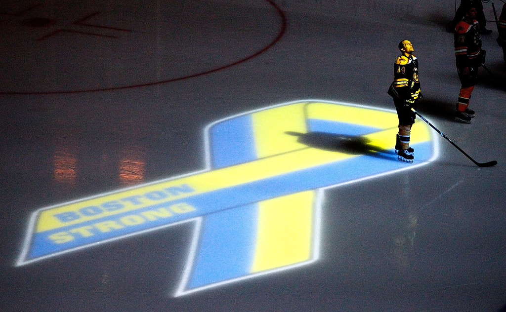 . BOSTON, MA - APRIL 17:  Dennis Seidenberg #44 of the Boston Bruins stands near aa projection of the Boston Marathon Memorial Ribbon seen on the ice during pre game ceremonies in remembrance of the Boston Marathon bombing victims before a game between the Buffalo Sabres and the Boston Bruins at TD Garden on April 17, 2013 in Boston, Massachusetts.  (Photo by Jim Rogash/Getty Images)