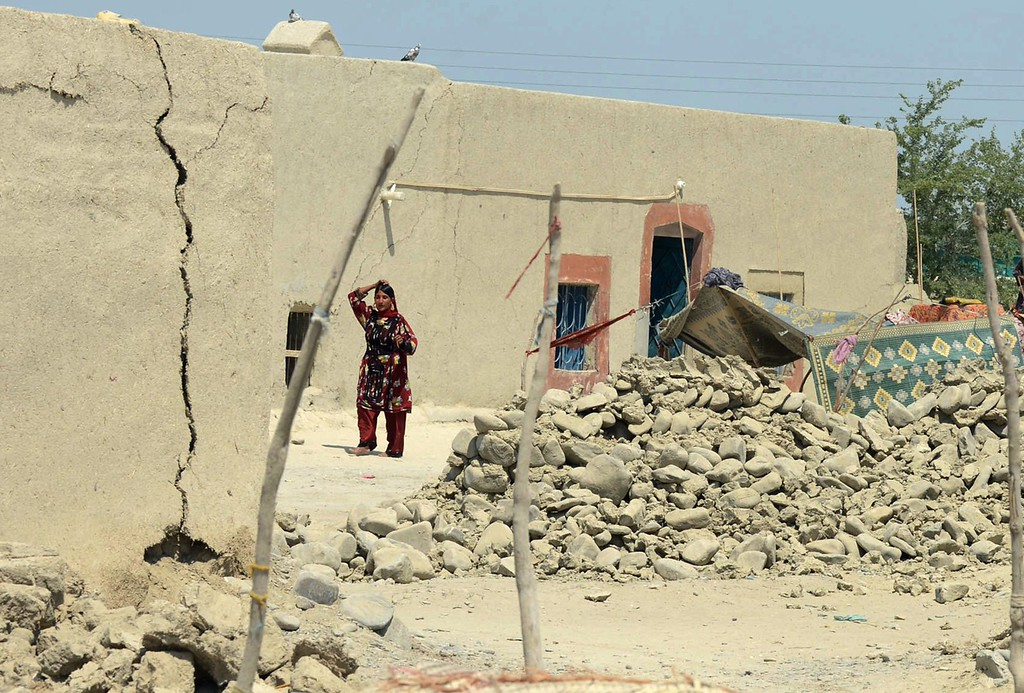 Description of . A Pakistani earthquake survivor walks past collapsed mud houses at Labach area, in the earthquake-devastated district of Awaran on September 26, 2013.  AFP PHOTO / Banaras KHAN/AFP/Getty Images