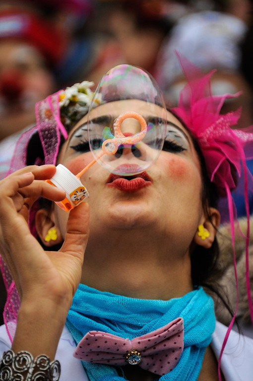 Description of . One of the clowns blows bubbles as some 2OO