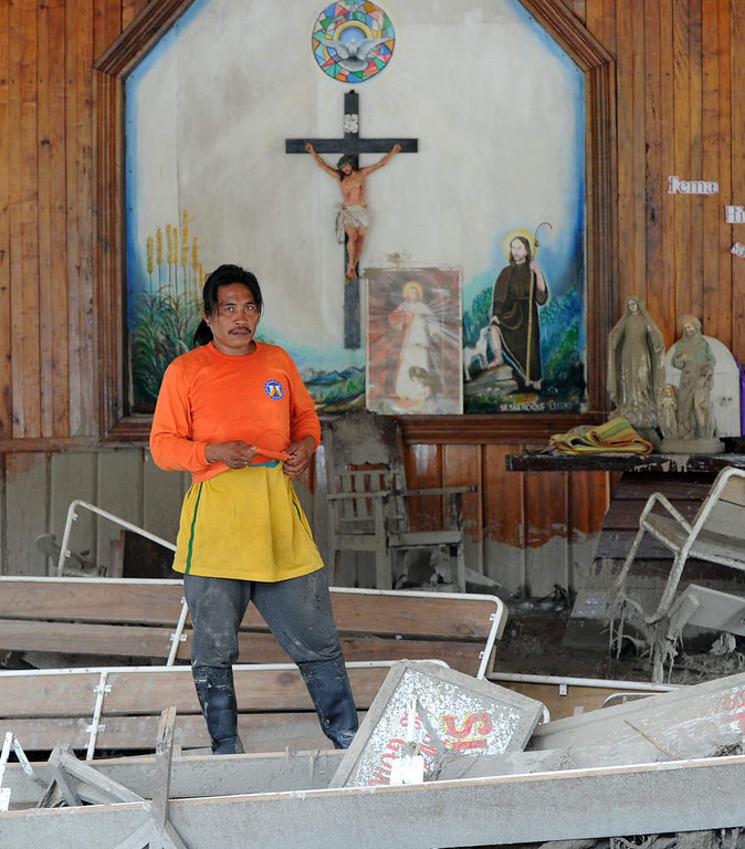 Description of . A rescue worker stands inside a church littered with debris swept in by flash floods caused by Typhoon Bopha in the village of Andap in the town of New Bataan in Compostela Valley province on December 8, 2012.  Hungry and homeless typhoon survivors appealed for help on December 8 as the ravaged southern Philippines mourned its more than 500 dead and desperate people in one hard-hit town looted shops in search of food.     AFP PHOTO / TED  ALJIBE/AFP/Getty Images