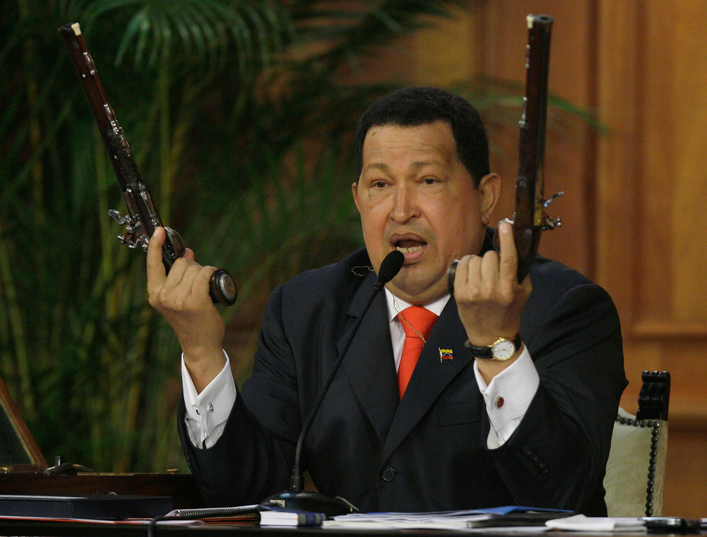 Description of . In this July 24, 2012 file photo, Venezuela's President Hugo Chavez holds up a pair of pistols that he says belonged to Venezuela's independence hero Simon Bolivar during a ceremony marking 229th anniversary of Bolivar's birth at Miraflores presidential palace in Caracas, Venezuela.  Bolivar is the namesake of Chavez's Bolivarian Revolution movement, and his government is putting the finishing touches on a new mausoleum to house Bolivar's remains. (AP Photo/Fernando Llano, File)