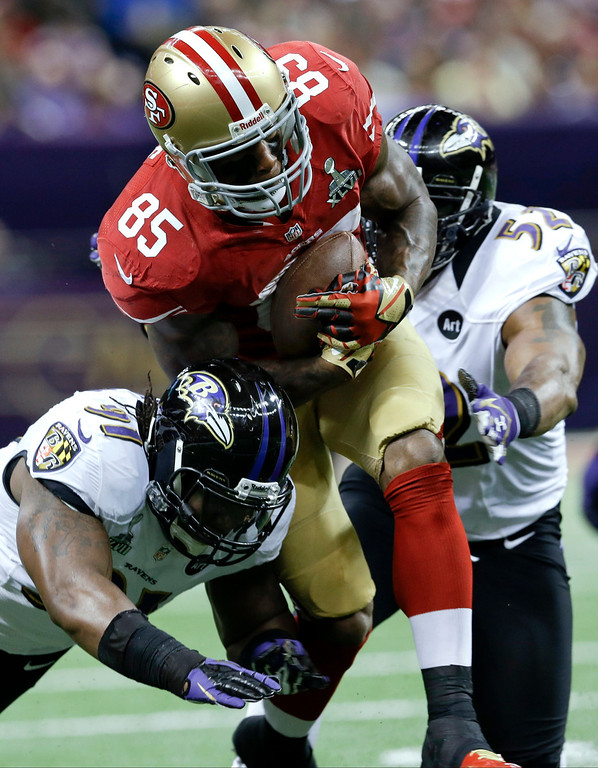 Description of . San Francisco 49ers tight end Vernon Davis (85) runs between Baltimore Ravens linebacker Courtney Upshaw, left, and Ray Lewis during the first half of the NFL Super Bowl XLVII football game, Sunday, Feb. 3, 2013, in New Orleans. (AP Photo/Patrick Semansky)