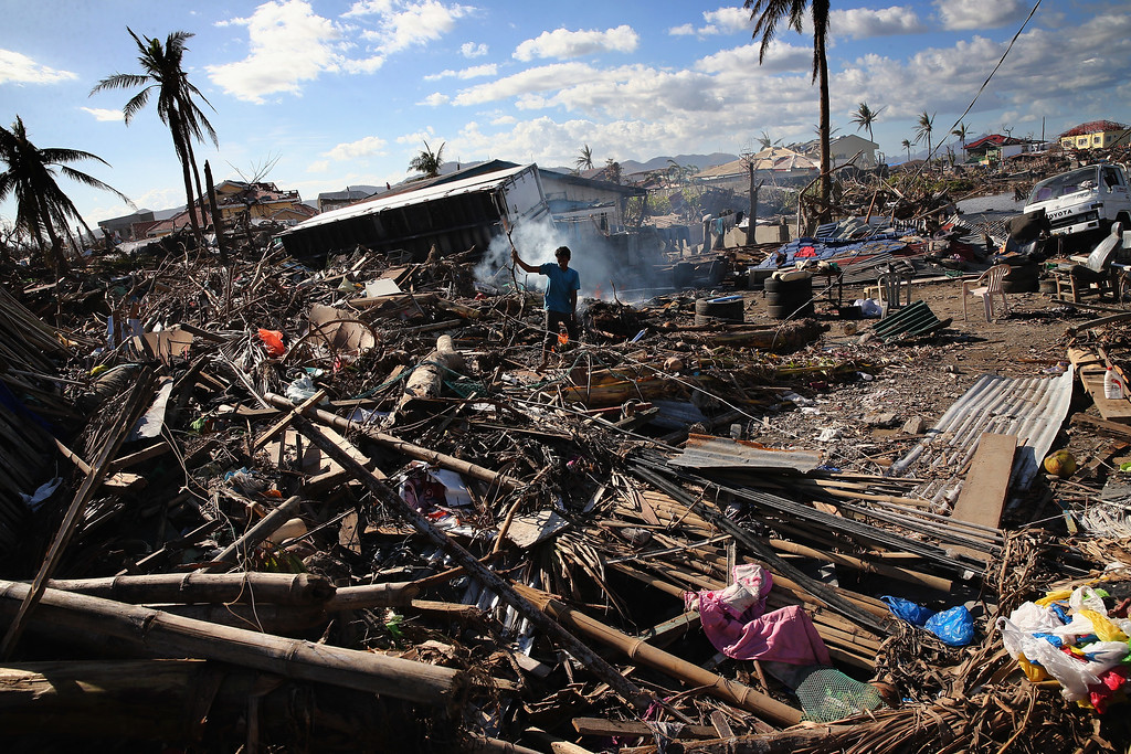 Description of . A man sifts through debris on November 15, 2013 in Leyte, Philippines.  (Photo by Dan Kitwood/Getty Images)