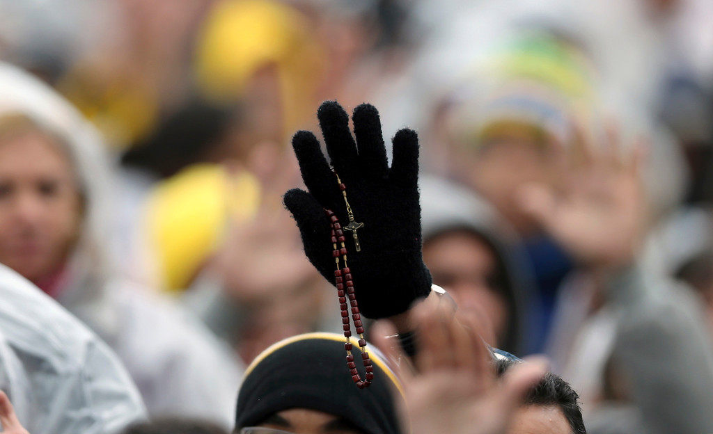 Description of . A person holds up a rosary during Mass celebrated by Pope Francis outside the Aparecida Basilica in Aparecida, Brazil, Wednesday, July 24, 2013. The church is struggling in Latin America to keep Catholics from straying to evangelical and Pentecostal churches that often promise help in finding material wealth, an alluring attraction in a poverty-wracked continent. Francis' top priority as pope has been to reach out to the world's poor and inspire Catholic leaders to go to slums and other peripheries to preach. (AP Photo/Andre Penner)