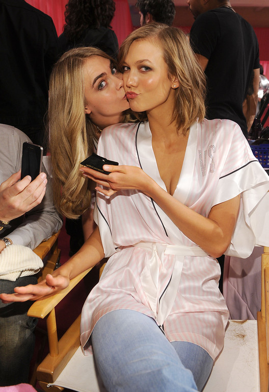 Description of . Models Cara Delevingne and Karlie Kloss pose at the 2013 Victoria's Secret Fashion Show hair and makeup room at Lexington Avenue Armory on November 13, 2013 in New York City.  (Photo by Jamie McCarthy/Getty Images)