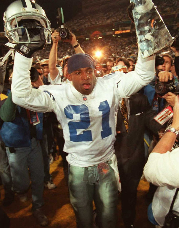 Description of . TEMPE, AZ - JANUARY 28:  Dallas Cowboys cornerback Deion Sanders hoists the Vince Lombardi Super Bowl trophy as he walks off the field to the locker room after defeating the Pittsburgh Steelers 28 January during Super Bowl XXX at Sun Devil Stadium in Tempe, Arizona. The Cowboys won 27-17. VINCE BUCCI/AFP/Getty Images