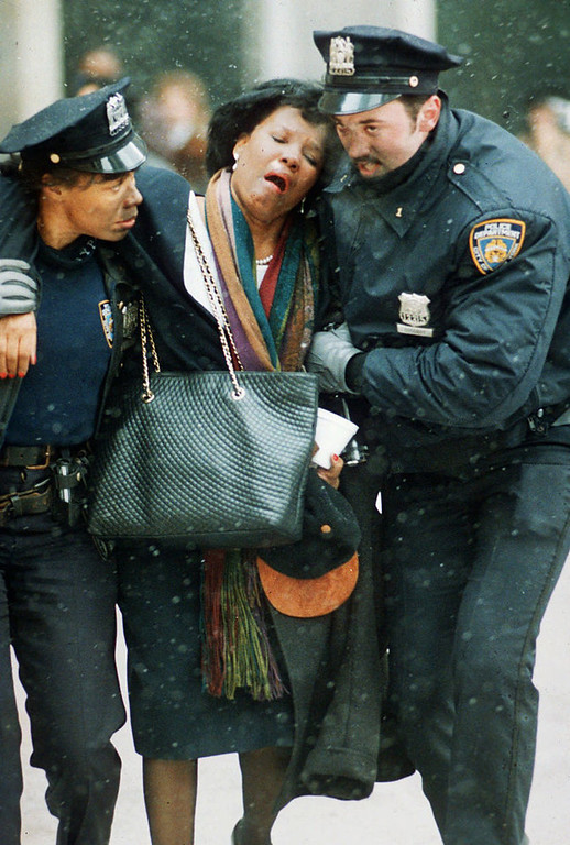 Description of . Two New York City police officers help an injured women away from the scene of the World Trade Center explosion on February 26, 1993. A group of terrorists blew up explosives in an underground parking garage under one of the towers, killing six people and ushering in an era of terrorism on American soil.  (AP Photo/Joe Tabacca, File)