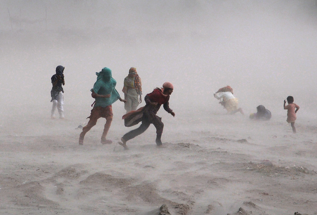 Description of . Pakistani people walk through a storm near the Ravi river in Lahore on September 15, 2013. Heavy rains and hailstorms lashed the capital, throwing traffic out of gear in many parts of the city as a result of water logging.   Arif Ali/AFP/Getty Images