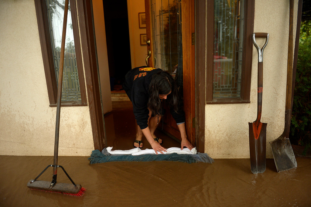 Description of . BOULDER, CO. - September 12: Tana Calderon-Griek  using towels to direct water from Four Mile Creek away from her father's home near Upland and 19th St. in Boulder after overnight rains caused flash flooding and damage in Boulder, September 12, 2013 in Boulder, Colorado. (Photo By Joe Amon/The Denver Post)