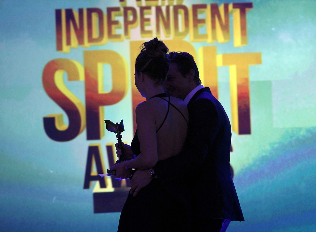Description of . Presenter Jeremy Renner and actress Jennifer Lawrence walk off the stage after she accepted the award for best female lead for
