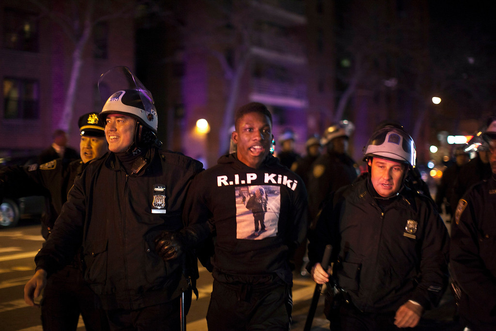 Description of . New York Police Department (NYPD) officers arrest a man during a protest against the killing of 16-year-old Kimani