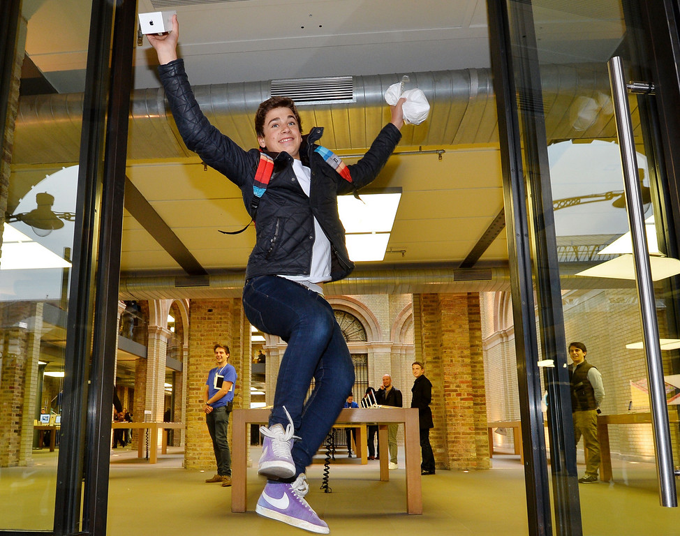 Description of . Jesse Green from London jumps as he leaves with his iPhone 5S after being the second person to enter the Apple store after they went on sale in central London on September 20, 2013.   Apple's eagerly-awaited iPhone 5S and 5C went on sale in London at 8am. AFP PHOTO / BEN  STANSALL/AFP/Getty Images