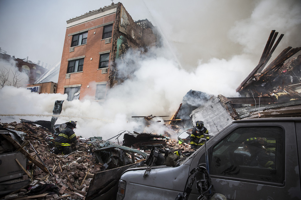 Description of . Heavy smoke pours from the debris as the Fire Department of New York (FDNY) responds to a 5-alarm fire and building collapse at 1646 Park Ave in the Harlem neighborhood of Manhattan March 12, 2014 in New York City. Reports of an explosion were heard before the collapse of two multiple-dwelling buildings that left at least 11 injured.  (Photo by Andrew Burton/Getty Images)