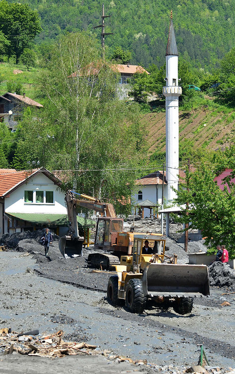 Description of . Workers use a backhoe and a bulldozer to clear the earth after a landslide in the flooded village of Topcic Polje, near the northern Bosnian city of Doboj, on May 19, 2014, after the river Bosna flooded entire agricultural fields and several urban areas along its flow during the weekend's rainfall, which also caused landslides. Thousands crammed into boats and army trucks as they fled their homes in Serbia and Bosnia on MAy 18 after record rainfalls. Officials say the disaster has killed at least 44 people so far.  AFP PHOTO / ELVIS BARUKCIC/AFP/Getty Images