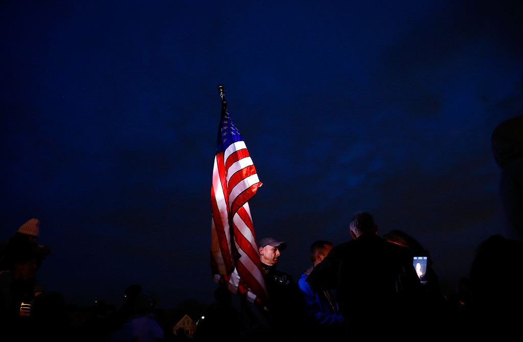 Description of . BOSTON, MA - APRIL 16: A man carries a large American flag during a vigil for eight-year-old Martin Richard, from Dorchester, who was killed by an explosion near the finish line of the Boston Marathon on April 16, 2013 at Garvey Park in Boston, Massachusetts. The twin bombings resulted in the deaths of three people and hospitalized at least 128. The bombings at the 116-year-old Boston race resulted in heightened security across the nation with cancellations of many professional sporting events as authorities search for a motive to the violence. (Photo by Jared Wickerham/Getty Images)