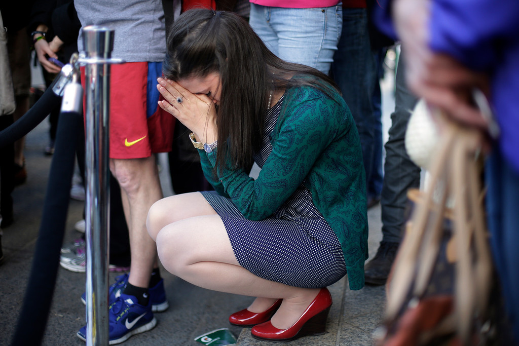 Description of . Jennifer Krewalk attends a makeshift memorial on Boylston Street near the finish line of Monday's Boston Marathon explosions, which killed at least three and injured more than 140,  Wednesday, April 17, 2013, in Boston. (AP Photo/Matt Rourke)