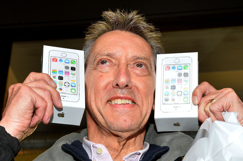 Description of . Norman Hicks from London is poses with two iPhone 5S's after being the first person to enter the Apple store after they went on sale in central London on September 17, 2013,   Apple's eagerly-awaited iPhone 5S and 5C went of sale in London at 8am. AFP PHOTO / BEN STANSALL/AFP/Getty Images
