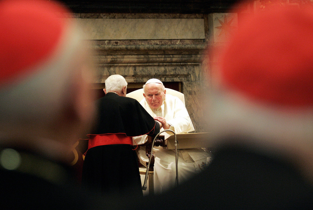 Description of . Cardinal Joseph Ratzinger (C) greets Pope John Paul II, during a special audience for the Roman curia before Christmas Eve in the Clementine hall at the Vatican, 21 December 2004. The 84-year-old Pontiff in his speech addressed Cardinals and Bishops to help him during his pontifical mission. ALBERTO PIZZOLI/AFP/Getty Images