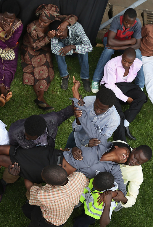 Description of . An emotionally distraught woman is carried out of Amahoro Stadium during the 20th anniversary commemoration of the 1994 genocide April 7, 2014 in Kigali, Rwanda.  (Photo by Chip Somodevilla/Getty Images)