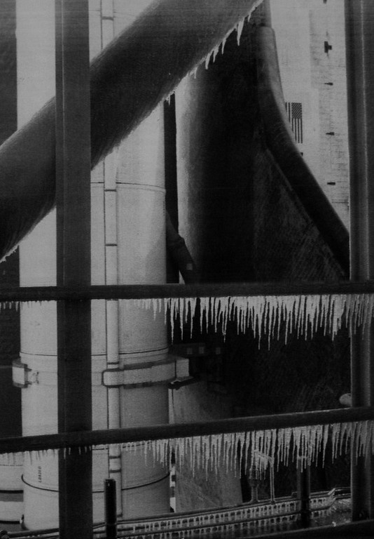 Description of . Icicles on the Challenger's launch pad on the morning of the ill-fated launch in this photo taken by a the Nasa ice inspection team. The icicles are on hand rails and the support structure. The shuttle, external fuel tank and left hand solid rocket booster motor are visible in the background. This is one of the pictures which the presidential commission investigating the disaster used in their investigations. Denver Post Library Archive