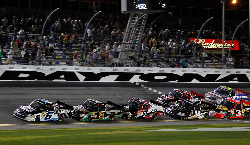 Description of . Justin Lofton (6), Ron Hornaday Jr. (9), Kyle Busch (51), Brennan Newberry (14), Ty Dillon (3), James Buescher, second row left, and Miguel Paludo, of Brazil, begin their fifth lap in the NASCAR Truck Series auto race at Daytona International Speedway, Friday, Feb. 22, 2013, in Daytona Beach, Fla. (AP Photo/Terry Renna)