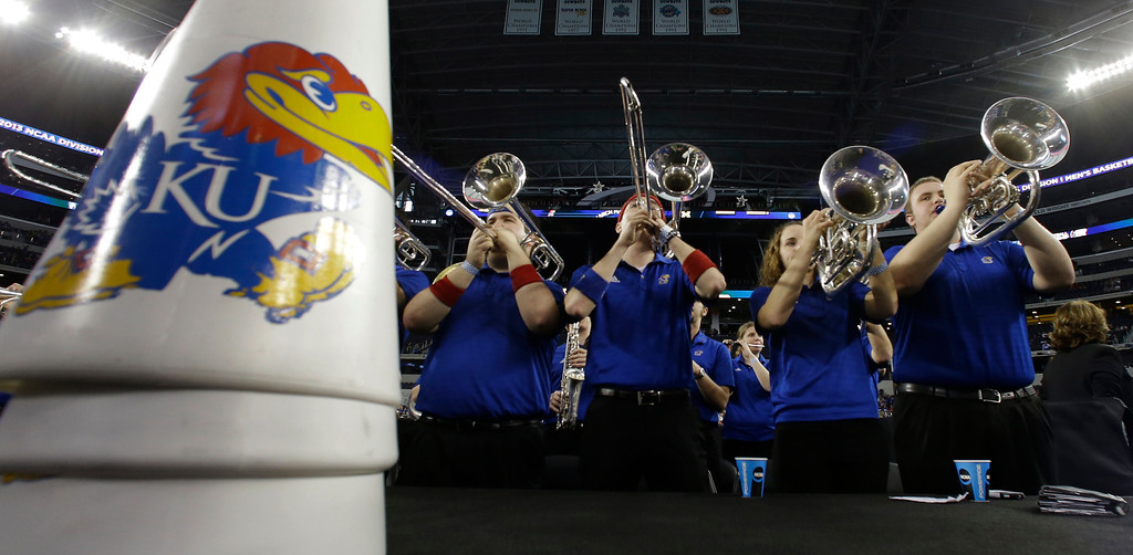 Description of . The Kansas band plays before a regional semifinal game against the Michigan in the NCAA college basketball tournament, Friday, March 29, 2013, in Arlington, Texas. (AP Photo/Tony Gutierrez)