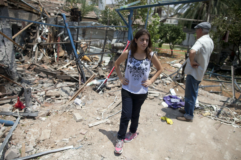 Description of . An Israeli woman inspects an Israeli home allegedly hit by a Hamas rocket  on July 22, 2014 in Yahud south to Tel Aviv, Israel. As operation 'Protective Edge' goes into it's third week, the death toll continues to mount, including 27 Israeli soldiers and over 500 people in Gaza, the vast majority of whom are civilians.  (Photo by Lior Mizrahi/Getty Images)