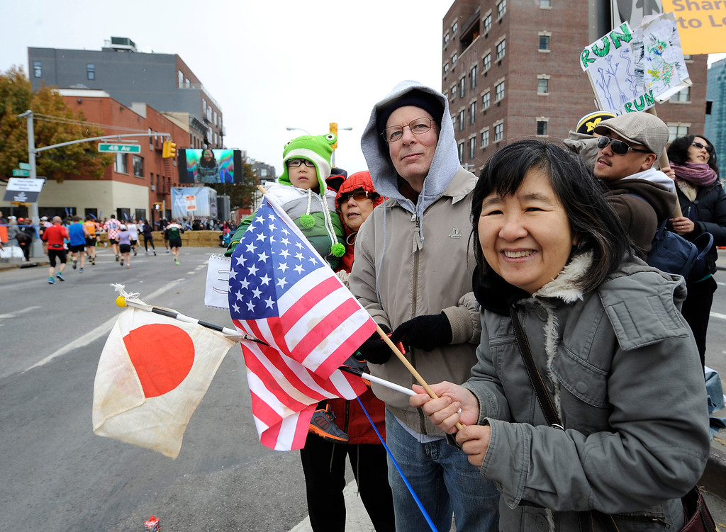 Description of . Junko Savage and her husband, Gary Savage of Little Neck, N.Y., cheer runners as they come off the Pulaski Bridge in the Queens borough of New York during the New York City Marathon on Sunday, Nov. 3, 2013.  (AP Photo/Kathy Kmonicek)