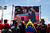 Supporters of Venezuela's late President Hugo Chavez watch a screen as Iran's President Mahmoud Ahmadinejad walks past Chavez's coffin during the funeral ceremony, outside the Military Academy in Caracas March 8, 2013.  REUTERS/Marco Bello