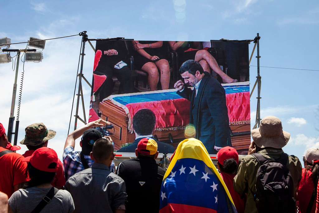 Description of . Supporters of Venezuela's late President Hugo Chavez watch a screen as Iran's President Mahmoud Ahmadinejad walks past Chavez's coffin during the funeral ceremony, outside the Military Academy in Caracas March 8, 2013.  REUTERS/Marco Bello