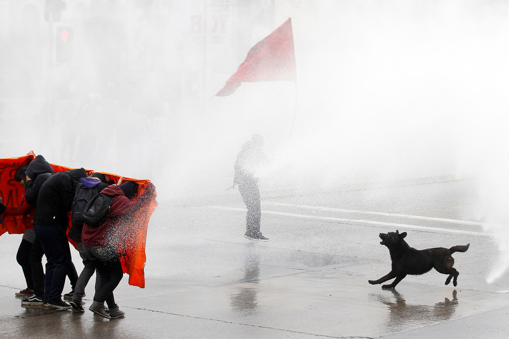 Description of . Student protesters are hit by a jet of water as they clash with riot policemen during a demonstration against the government to demand changes in the public state education system in Santiago, August 23, 2012. Chilean students have been protesting against what they say is profiteering in the state education system. REUTERS/Ivan Alvarado