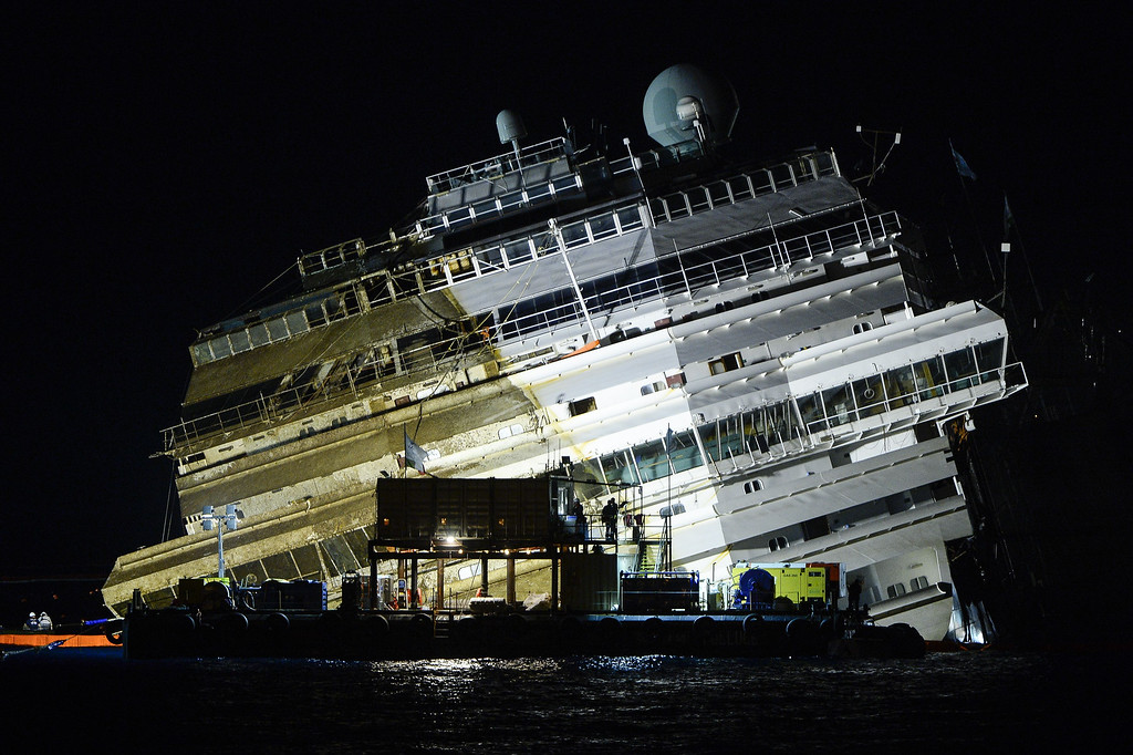 Description of . The wreck of Italy's Costa Concordia cruise ship begins to emerge from water on September 17, 2013 near the harbour of Giglio Porto.  ANDREAS SOLARO/AFP/Getty Images