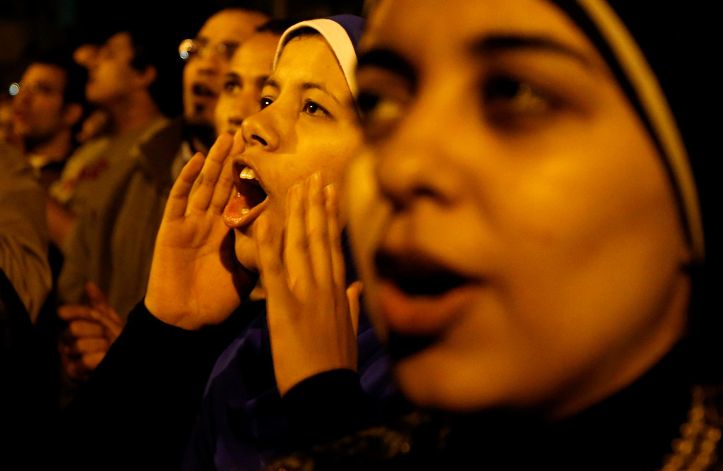 Description of . Protesters chant slogans during a demonstration in front of the presidential palace in Cairo, Egypt, Sunday, Dec. 9, 2012. Egypt\'s liberal opposition called for more protests Sunday, seeking to keep up the momentum of its street campaign after the president made a partial concession overnight but refused its main demand he rescind a draft constitution going to a referendum on Dec. 15. (AP Photo/Petr David Josek)