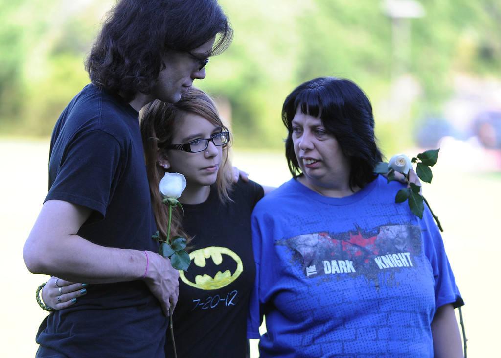 Description of . AURORA, CO - JULY 20:  From left to right, Brian Lacey, Stephaney <cq> Wacker, 18, and Stephaney's mother, Cheryl Wacker, at the 7/20 Day of Remembrance 2013 at the Aurora Municipal Center Saturday morning, July 20, 2013. Over 200 people attended the service in honor of the 12 people killed and over 60 people injured in last years Aurora theater shooting. The service included prayer, songs and speeches from local officials and the Governor of Colorado, John Hickenlooper. Stephaney Wacker's close friend, AJ Biok was killed in the shooting July 20, 2012.  (Photo By Andy Cross/The Denver Post)