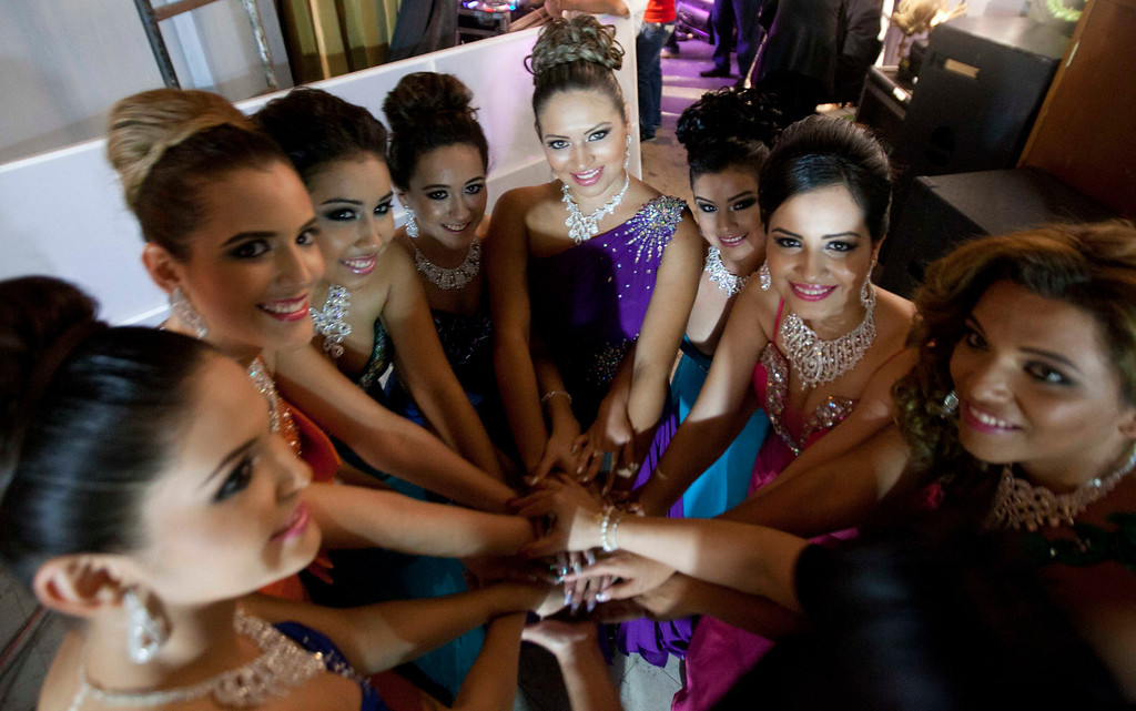 Description of . In this Jan. 26, 2013 photo, Magdabelyn Parra Gamez, who goes by Belyn, second from right, poses for photos with fellow beauty contestants backstage at the beauty pageant