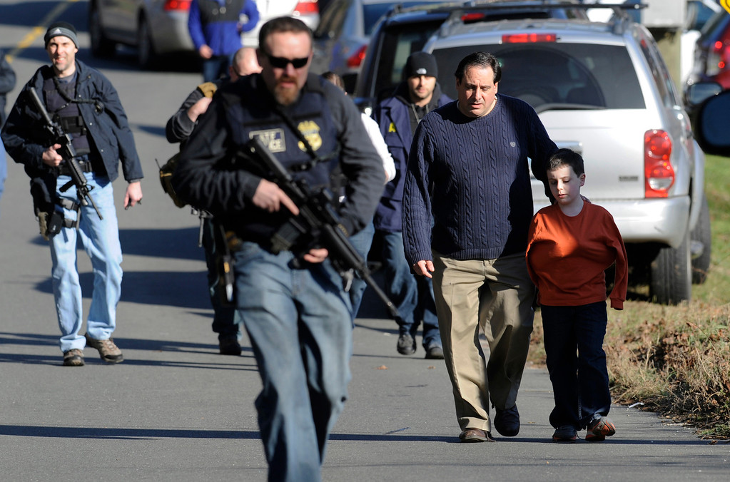 Description of . Parents leave a staging area after being reunited with their children following a shooting at the Sandy Hook Elementary School in Newtown, Conn., about 60 miles (96 kilometers) northeast of New York City, Friday, Dec. 14, 2012. An official with knowledge of Friday's shooting said 27 people were dead, including 18 children. It was the worst school shooting in the country's history. (AP Photo/Jessica Hill)
