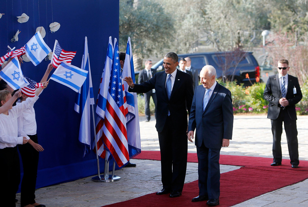 Description of . U.S. President Barack Obama (C) stands with Israel's President Shimon Peres on the red carpet during a welcoming ceremony at Peres' residence in Jerusalem March 20, 2013.REUTERS/Ronen Zvulun